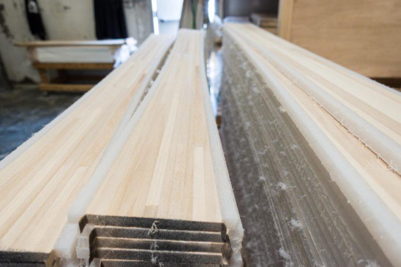 木材とプラスチックのような素材を貼り合わせたかたまりをスライスしていく